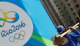 A construction worker walks by a logo of the Rio 2016 Olympics in Rio de Janeiro, Brazil, July 27, 2016.  REUTERS/Kai Pfaffenbach
