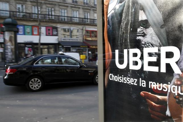 A taxi passes by an advertisement for the Uber car and ride-sharing service displayed on a bus stop in Paris, France, in this March 11, 2016 file photo. REUTERS/Charles Platiau/File Photo - RTX2GONB