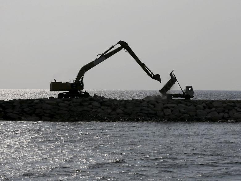 A tipper truck unloads rocks as part of a process to reclaim the sea front next to an excavator at ''Colombo Port City'' construction site, backed by Chinese investment, is seen in Sri Lanka April 7, 2016. REUTERS/Dinuka Liyanawatte/Files