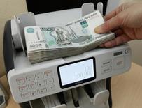 Кассир пересчитывает 1000-рублевые банкноты. Рубль показывает рост во вторник, следуя за развернувшейся вверх нефтью, с которой он восстановил корреляцию после завершения налогового периода и основной фазы дивидендного сезона, хотя локальные потоки также продолжают оказывать умеренное влияние на валютный рынок, по оценке его участников.  REUTERS/Ilya Naymushin