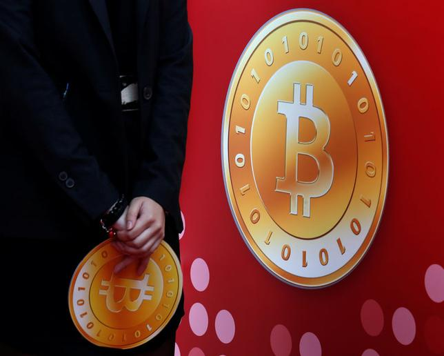 An attendant holds a bitcoin sign during the opening of Hong Kong's first bitcoin retail store February 28, 2014. REUTERS/Bobby Yip/File Photo