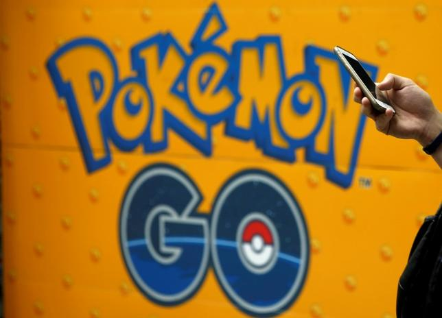 A man uses a mobile phone in front of an advertisement board bearing the image of Pokemon Go at an electronic shop in Tokyo, Japan, July 27, 2016.   REUTERS/Kim Kyung-Hoon