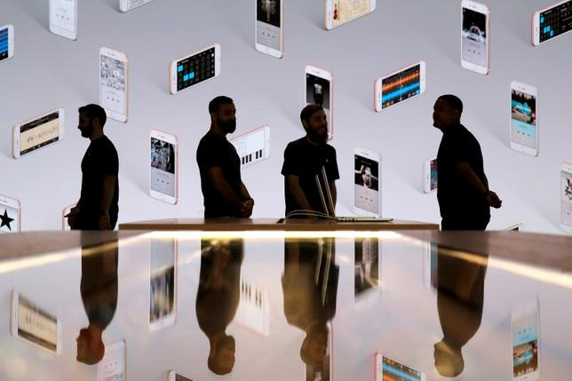 Store employees stand in front of a screen displaying iPhones during a preview event at the new Apple Store Williamsburg in Brooklyn, New York, U.S., July 28, 2016.  REUTERS/Andrew Kelly