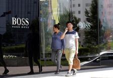 Hugo Boss a livré vendredi des résultats du deuxième trimestre supérieur aux attentes avec un bénéfice opérationnel ajusté en repli de 13% à 108 millions d'euros et un chiffre d'affaires en recul de 4% à 622 millions d'euros. La griffe allemande a par ailleurs annoncé qu'une vingtaine de boutiques supplémentaires seraient fermées, la stratégie de réduction des coûts du groupe semblant porter ses fruits. /Photo prise le 27 juin 2016/REUTERS/Jason Lee