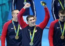 2016 Rio Olympics - Swimming - Victory Ceremony - Men's 4 x 100m Freestyle Relay Victory Ceremony - Olympic Aquatics Stadium - Rio de Janeiro, Brazil - 07/08/2016. Michael Phelps poses with his gold medal as he celebrates with his team.  REUTERS/Marcos Brindicci