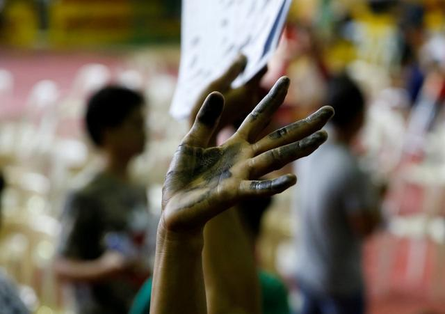 A drug user raises his ink smeared hand after he surrendered to local government officials to take part in a government campaign against drug in Tanauan Batangas, south of Manila, Philippines July 18, 2016. REUTERS/Erik De Castro