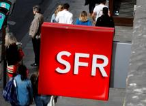 People walk under the logo of French telecoms operator SFR in Paris, France, August 8, 2016.  REUTERS/Philippe Wojazer - RTSLVBW
