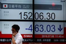 Un hombre que habla por celular pasa cerca de una pantalla que muestra el índice Nikkei de Japón, afuera de una correduría en Tokio, Japón. 6 de julio de 2016. El promedio bursátil Nikkei de Japón subió el martes y tocó su máximo nivel en dos semanas, ante un bajo volumen de transacciones debido a la debilidad del yen. REUTERS/Issei Kato