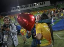 2016 Rio Olympics - Rugby - Women's Gold Medal Match Australia v New Zealand - Deodoro Stadium - Rio de Janeiro, Brazil - 08/08/2016.  Rugby player Isadora Cerullo (BRA) of Brazil hugs Marjorie, a volunteer, after receiving her wedding proposal on the sidelines of the women's rugby medal ceremony. REUTERS/Alessandro Bianchi