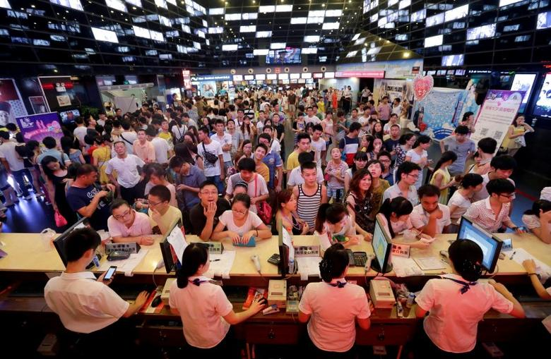 People wait for tickets at a ticket office of a movie theatre in Wuhan, Hubei province, August 13, 2013.  REUTERS/Darley Shen/File Photo