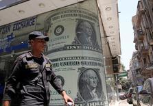 Devant un bureau de change au Caire. Le Fonds monétaire international (FMI) a annoncé jeudi avoir conclu avec l'Egypte un projet d'accord portant sur un programme de prêts de 12 milliards de dollars (10,8 milliards d'euros) sur trois ans, censé favoriser la mise en oeuvre de réformes structurelles. /Photo prise le 3 août 2016/REUTERS/Mohamed Abd El Ghany