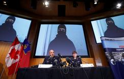 An image of Aaron Driver, a Canadian man killed by police on Wednesday who had indicated he planned to carry out an imminent rush-hour attack on a major Canadian city, is projected on screens during a news conference with Royal Canadian Mounted Police (RCMP) Deputy Commissioner Mike Cabana (L) and Assistant Commissioner Jennifer Strachan in Ottawa, Ontario, Canada, August 11, 2016. REUTERS/Chris Wattie