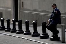 Трейдер отдыхает рядом со зданием фондовой биржи в Нью-Йорке. Фондовые индексы США снижаются в начале торгов в пятницу, на следующий день после роста до рекордных максимумов на момент закрытия с 1999 года, на фоне более слабых, чем ожидалось, экономических данных.  REUTERS/Brendan McDermid