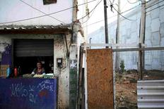 Maria, 71, waits for costumers at her kiosk next to the Transolimpica BRT, an express road built through a shantytown to join the Rio 2016 Olympic venues of Deodoro and Barra da Tijuca, in the Vila Uniao favela of Rio de Janeiro, August 12, 2016. REUTERS/Nacho Doce