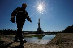 A worker walks past a drilling rig at a well pad of the Rosneft-owned Prirazlomnoye oil field outside the West Siberian city of Nefteyugansk, Russia, August 4, 2016. REUTERS/Sergei Karpukhin/File Photo