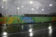 Voluntário caminha na chuva no Parque Olímpico do Rio de Janeiro 10/08/2016 REUTERS/Kevin Coombs