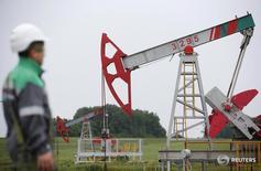 A worker looks at a pump jack at an oil field Buzovyazovskoye owned by Bashneft company north from Ufa, Bashkortostan, Russia, July 11, 2015. REUTERS/Sergei Karpukhin/File Photo - RTX2FAFF