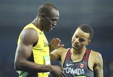 Bolt e Andre De Grasse após 200m na Rio 2016.  18/08/2016.  REUTERS/Lucy Nicholson