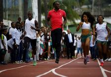 """Jamaican Olympic gold medallist Usain Bolt (C) runs with youths at the Mangueira slum Olympic center, ahead of the """"Mano a Mano"""" challenge, a 100-meter race, in Rio de Janeiro, Brazil, April 16, 2015. REUTERS/Ricardo Moraes/File Photo"""