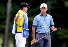 Aug 21, 2016; Greensboro, NC, USA; Si Woo Kim (right) waits to putt on the ninth hole during the final round of the 2016 Wyndham Championship at Sedgefield Country Club. Mandatory Credit: Rob Kinnan-USA TODAY Sports