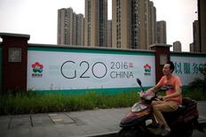 A man rides an electronic bike past a billboard for the upcoming G20 summit in Hangzhou, Zhejiang province, China, July 29, 2016. Picture taken July 29, 2016. REUTERS/Aly Song