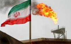 Флаг Ирана на фоне газового факела на нефтяном месторождении Сороуш в Персидском Заливе 25 июля 2005 года. Иран поможет другим нефтепроизводителям стабилизировать мировой рынок, если другие представители ОПЕК признают его право на восстановление доли рынка, сказал министр нефти в пятницу. REUTERS/Raheb Homavandi/File Photo
