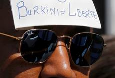 "A man wears a placard with the message, ""Burkini = Liberty"" outside the Conseil d'Etat after France's highest administrative court suspended a ban on full-body burkini swimsuits that has outraged Muslims and opened divisions within the government, pending a definitive ruling, in Paris, France, August 26, 2016. REUTERS/Regis Duvignau"