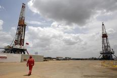 Un trabajador camina cerca de perforadors en un campo petrolero en el cinturon del Orinoco en el estado de Monagas en Venezuela. 16 de abril de 2015. La estatal Petróleos de Venezuela (PDVSA) relanzó una licitación para perforar 600 pozos petroleros en sus vastas reservas, dijeron esta semana fuentes con conocimiento del negocio a Reuters, luego de que una oferta similar colapsó el año pasado por preocupaciones sobre su transparencia. REUTERS/Carlos Garcia Rawlins