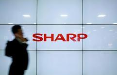 A man using his mobile phone walks past Sharp Corp's liquid crystal display monitors showing the company logo in Tokyo, Japan, March 30, 2016. REUTERS/Yuya Shino/File Photo