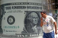 Мужчина проходит мимо изображения долларовой купюры в Каире 3 августа 2016 года. Доллар устойчив на торгах в Азии в понедельник, поскольку оптимистичные комментарии главы Федеральной резервной системы США Джанет Йеллен о состоянии американской экономики усилили ожидания повышения ключевой ставки. REUTERS/Mohamed Abd El Ghany