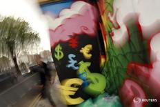 Символы различных валют на стене в Дублине 22 октября 2014 года. Доллар колеблется к иене и евро в четверг в преддверии публикации данных о занятости в США без учёта сельскохозяйственного сектора в пятницу, которые, как ожидается, могут оказать влияние на перспективы повышения ставок ФРС. REUTERS/Cathal McNaughton
