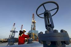 A worker checks an oil pipe at the Lukoil-owned Imilorskoye oil field outside the West Siberian city of Kogalym, Russia, in this January 25, 2016 file photo.   REUTERS/Sergei Karpukhin