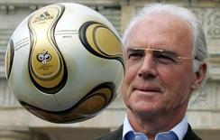 Franz Beckenbauer, President of Germany's World Cup organising committee, plays with a golden soccer ball during a presentation next to the Brandenburg gate in Berlin April 18, 2006.      REUTERS/Tobias Schwarz/File Photo