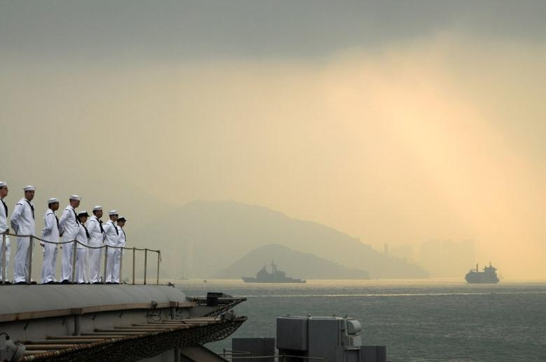 Sailors aboard the aircraft carrier USS George Washington man the rails as the ship pulls out of Hong Kong.  REUTERS/U.S. Navy