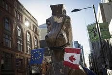 """A giant Trojan horse statue holding EU and Canadian flags in its mouth, set up by the social activist group """"Council of Canadians"""" in front of the Ontario Investment and Trade Centre to protest the Comprehensive Economic and Trade Agreement (CETA) between Canada and the European Union, is seen in Toronto November 4, 2013.    REUTERS/Mark Blinch"""