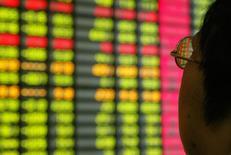 Инвестор в брокерской конторе в Шанхае 12 ноября 2003 года. Китайские акции существенно укрепились в четверг, поскольку решение Федрезерва США сохранить ключевую ставку без изменений ослабило беспокойства инвесторов. REUTERS/Claro Cortes IV/File Photo