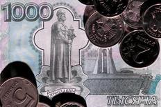 Рублевые монеты и 1000-рублевая купюра. Рубль начал торговую сессию в пятницу ослаблением к доллару, следуя за дешевеющей нефтью. REUTERS/Maxim Zmeyev/Illustration