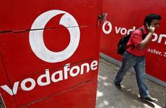 Vodafone está reforzándose para una gran batalla en la India. El gigante de la telefonía móvil va a inyectar 7.200 millones de dólares en efectivo en su filial india en lo que según la empresa es la inversión directa extranjera más grande de la historia en el país. En esta imagen de archivo, un hombre habla por el móvil mientras camina ante los logos de Vodafone en Calcuta, el 20 de mayo de 2014. REUTERS/Rupak De Chowdhuri