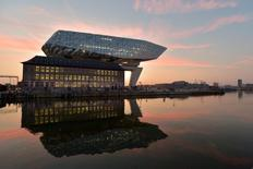 The sun rises behind the new headquarters for the Antwerp Port Authority on the Kattendijk dock, the Port House, a monumental design by Zaha Hadid Architects in Antwerp, Belgium September 22, 2016. Reuters/Eric Vidal     TPX IMAGES OF THE DAY