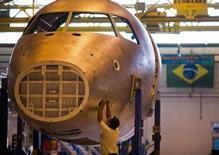 Un técnico trabaja en un avión en la línea de ensamblaje de Embraer, en Sao José dos Campos, 16 de octubre de 2014. El fabricante brasileño de aeronaves Embraer SA confirmó el lunes que recortará casi un 8 por ciento de su fuerza laboral a través de un programa voluntario, en medio de una disminución de costos por débiles ventas de aviones para ejecutivos y contratos de defensa reducidos. REUTERS/Roosevelt Cassio