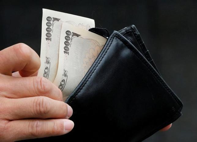 8月30日、総務省が発表した8月の家計調査によると、全世帯(単身世帯除く2人以上の世帯)の実質消費支出は前年比4.6%減となった。減少は6カ月連続。実額は27万6338円。写真は1万円札を取り出す男性、2012年11月撮影(2016年 ロイター/Kim Kyung-Hoon)