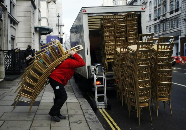 A man loads a van with stacks of gold painted chairs outside a hotel in London February 5, 2014. REUTERS/Luke MacGregor