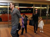Brad Pitt e Angelina Jolie com filhos no aeroporto de Tóquio.  28/7/2013.  REUTERS/Issei Kato