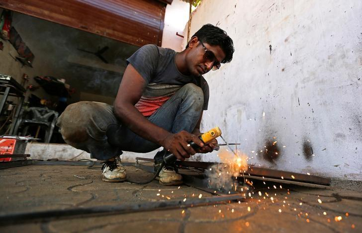 A worker welds a steel rod inside a door and window manufacturing unit on the outskirts of Ahmedabad, India, September, 12, 2016. REUTERS/Amit Dave/Files