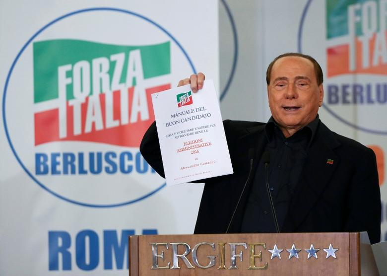 Former Italian prime minister Silvio Berlusconi shows a ''manual of the good candidate'' during a presentation of Rome's mayoral candidate Alfio Marchini (not seen) in Rome, Italy May 10, 2016.   REUTERS/Alessandro Bianchi /File Photo
