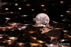 Рублевые монеты. Рубль обновил максимум текущего года к доллару на биржевой сессии понедельника благодаря нефти, чьи котировки приближались к отметке $51 за баррель Brent после договоренностей о заморозке добычи странами ОПЕК, а также благодаря снижению напряженности на рынках в надежде на соглашение Deutsche Bank с Минюстом США. REUTERS/Maxim Zmeyev/Illustration