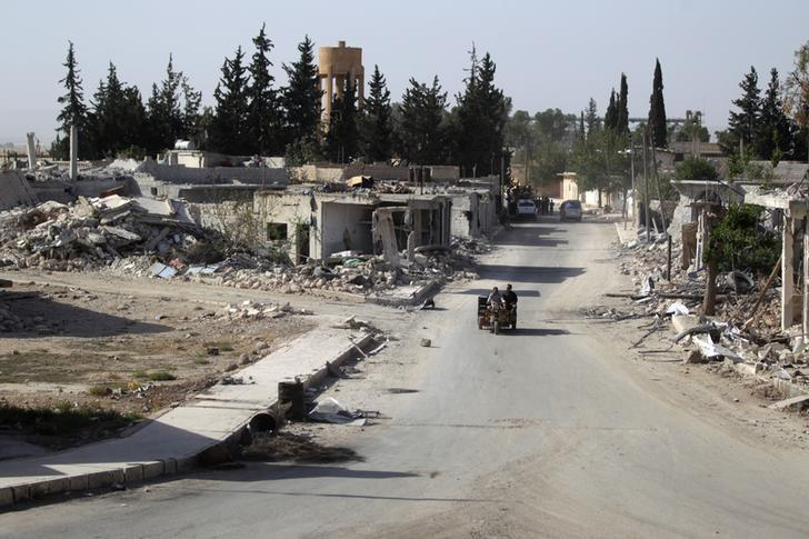 Vehicles drive past damaged buildings in al-Rai town, northern Aleppo countryside, Syria October 2, 2016. REUTERS/Khalil Ashawi