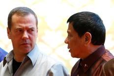 """Президент Филиппин Родриго Дутерте (справа) разговаривает с российским премьер-министром Дмитрием Медведевым на саммите ASEAN во Вьентьяне, Лаос, 7 сентября 2016 года. Дутерте во вторник предложил президенту США Бараку Обаме """"идти к черту"""" и добавил, что хотя Америка отказалась продавать Филиппинам некоторые виды оружия, его это не волнует, поскольку поставщиками легко станут Россия и Китай. REUTERS/Jorge Silva"""