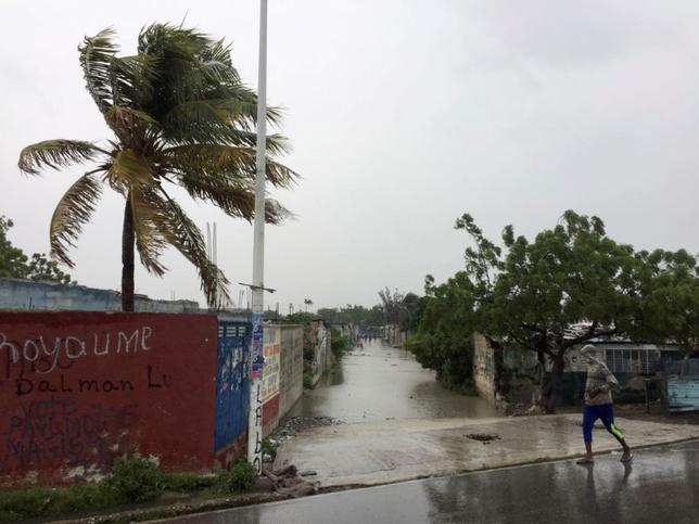 A man walks past a flooded street while Hurricane Matthew passes, in Cite-Soleil in Port-au-Prince, Haiti, October 4, 2016. REUTERS/Carlos Garcia Rawlins
