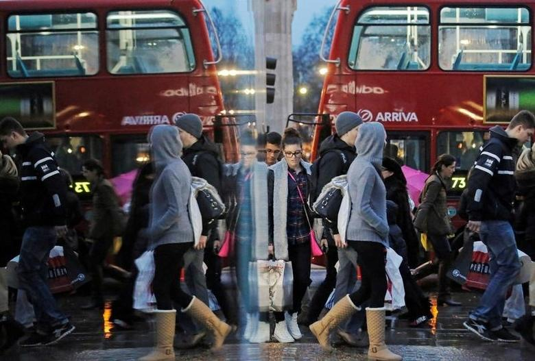 Shoppers are reflected in a shop window as they walk along Oxford Street on the last Saturday before Christmas, in London, Britain, December 21, 2013. REUTERS/Luke MacGregor/File Photo